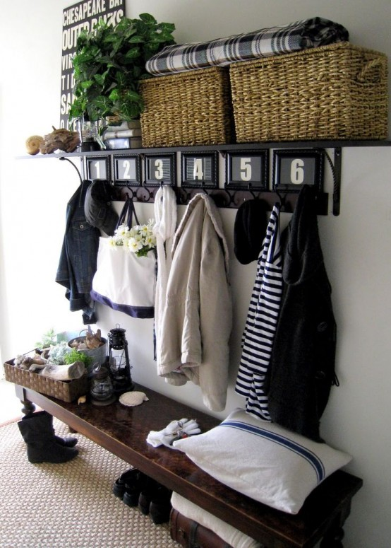 a modenr rustic entryway with a dark vintage bench, a rack with basket boxes and a jute rug