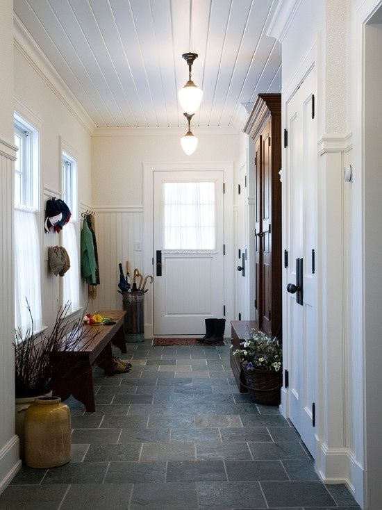a farmhouse mudroom done in white with a grey tile floor, dark furniture and soem branch arrangements