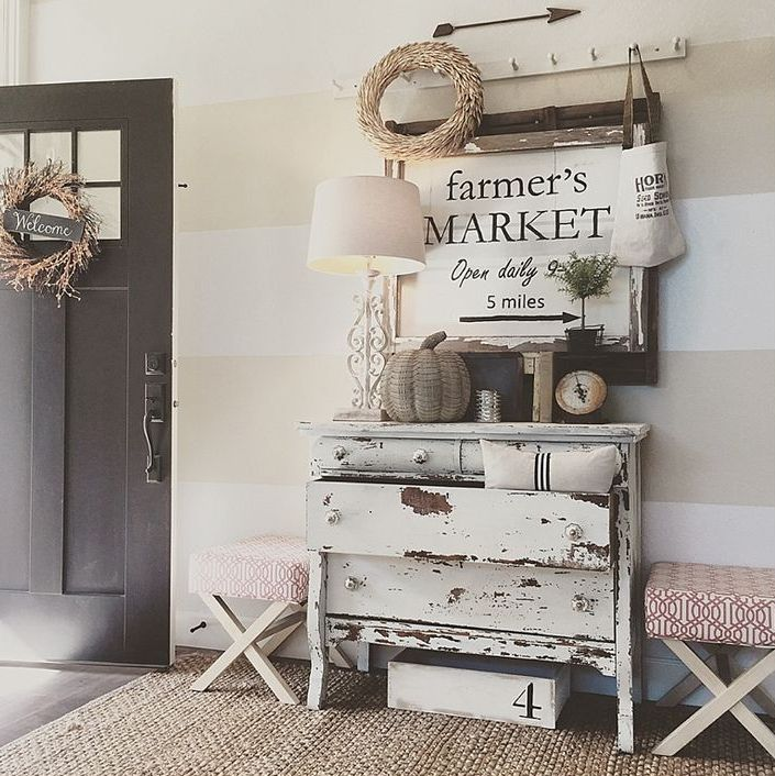 a shabby chic dresser, upholstered stools, a jute rug, a rack with hooks and a lamp plus some wreaths
