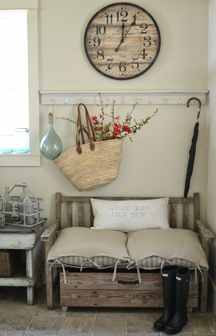 a farmhouse entryway with a wooden bench, a box on casters, a wooden clock and a rack with hooks