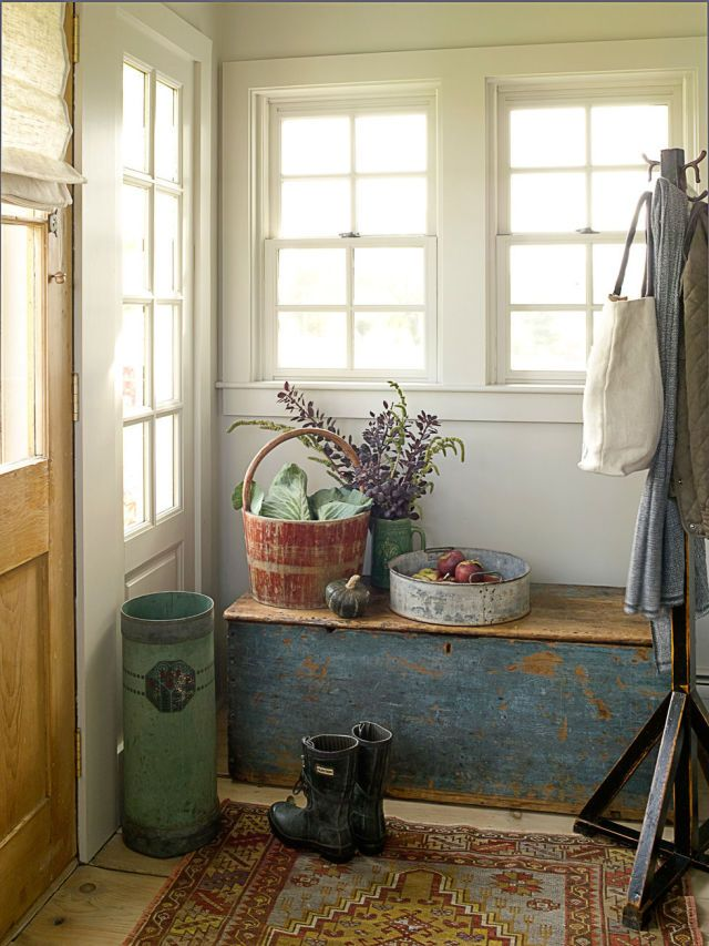 a rustic meets shabby chic entryway with a shabby blue chest, a rug and some wooden baskets for storage