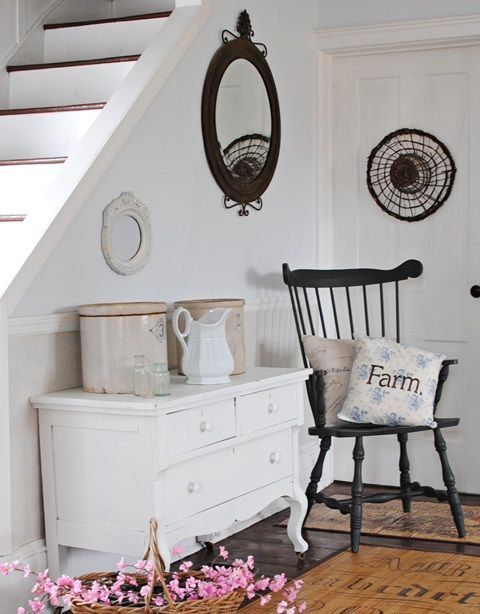 a white vintage sideboard, a black vintage chair, a round mirror and tin cans for storage plus a FARM pillow