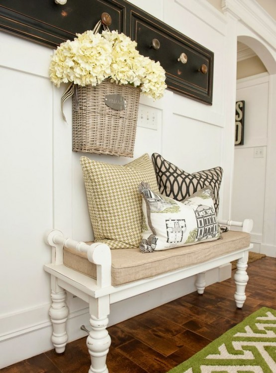 a vintage farmhouse entryway with racks with knobs, a vintage white bench with a burlap cushion and a rug
