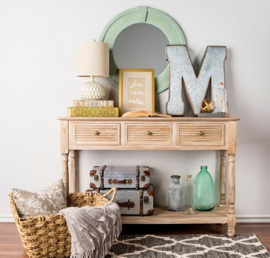 a cozy vintage meets rustic entryway with a woodne console, some metal suitcases, a metal monogram and a basket for storage