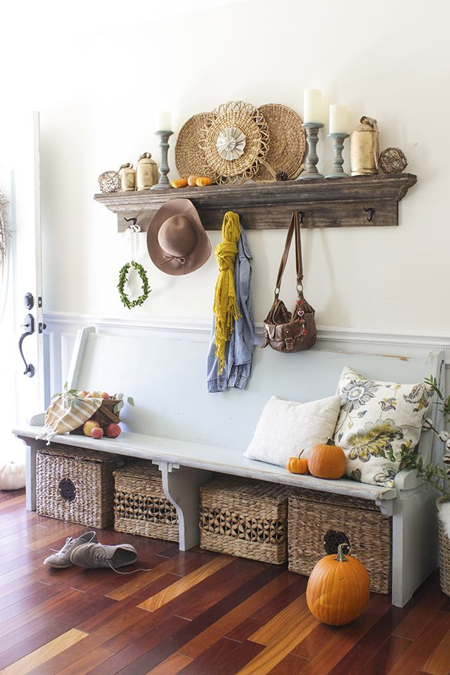 a cozy fall farmhouse entryway with a shabby chic bench, a stained open shelf, basket boxes for storage and candles