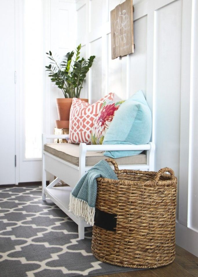 a cozy farmhouse entryway with a vintage white bench with colorful pillows, a wooden sign and a basket with blankets