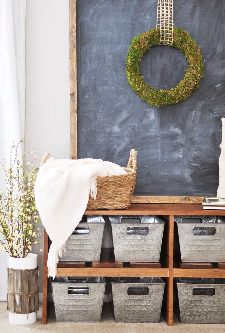 a simple farmhouse entryway with a large bench with metal boxes for storage and a chalkboard with a wreath on it