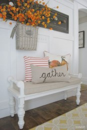 a small fall farmhouse entryway with a vintage white bench, bright pillows, a bold arrangement hanging on the rack