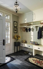 a farmhouse entryway with an ivory wooden furniture piece iwth a built-in bench of drawers and more storage space plus dark tiles on the floor for a contrast