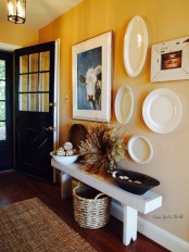 a vintage meets rustic entryway with a white bench, a gallery wall with decorative plates and artworks, a basket and a jute rug