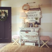a shabby chic meets farmhouse entryway with a white dresser, wreaths, pumpkins and a large artwork
