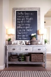 a weathered wood console table with drawers, a striped rug, baskets for storage, lamps and a framed chalkboard sign