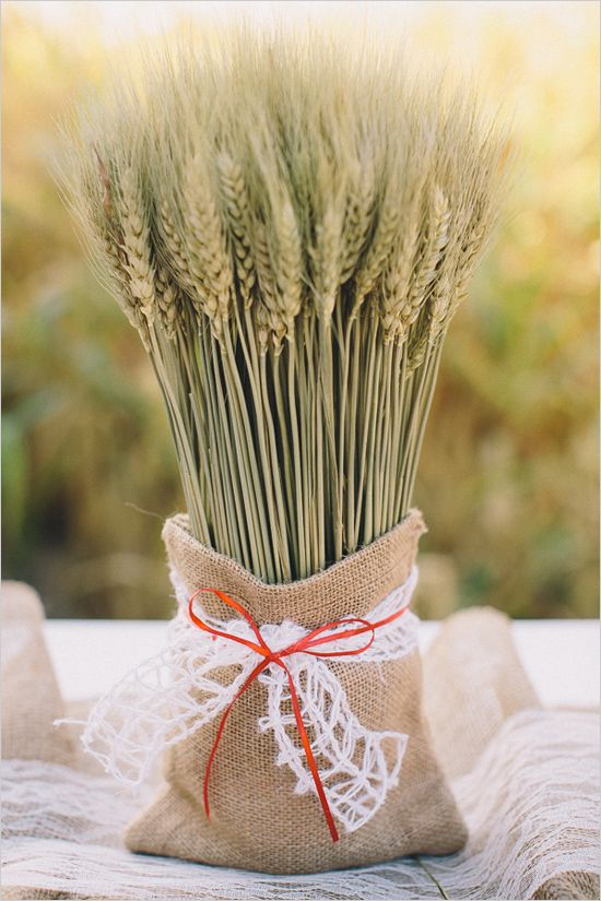 a wheat arrangement in a burlap sack with lace is a chic and simple decoration or a centerpiece for the fall