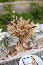 a beautiful wheat and feather arrangement with a silk ribbon is a chic rustic centerpiece