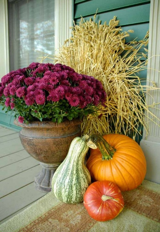 farmhouse porch decor with gourds, pumpkins, purple blooms in a vintage urn and a wheat arrangement placed behind them