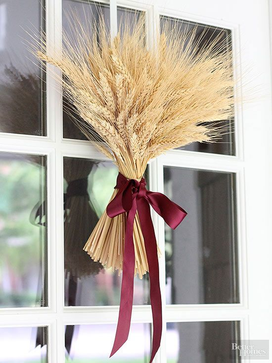 a wheat arrangement with a purple ribbon bow can be hung on your front door instead of a usual wreath to make it amazingly fall-like