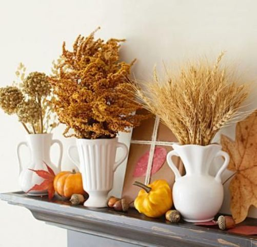 fall mantel decor with nuts, acorns, pumpkins, leathers and white vases and jugs with dried blooms and wheat is warm and cozy