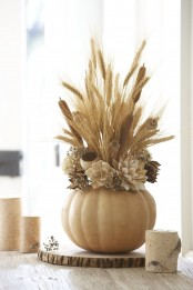 a wood slice with a neutral pumpkin with dried blooms, cane, wheat and dried herbs is a neutral farmhouse arrangement and centerpiece