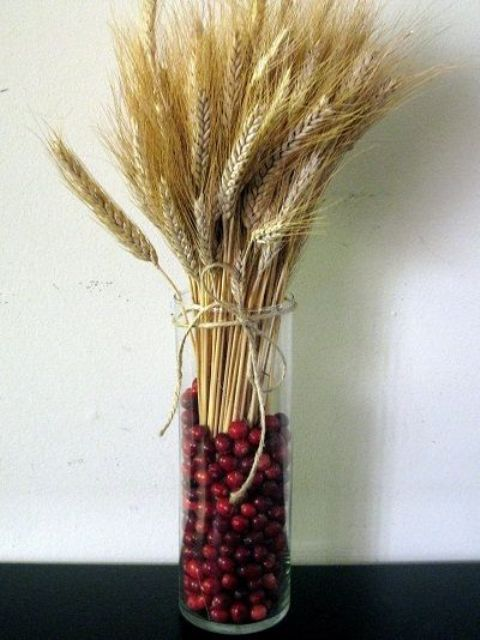 a tall glass vase with cranberries and wheat is a lovely centerpiece and decoration for the fall