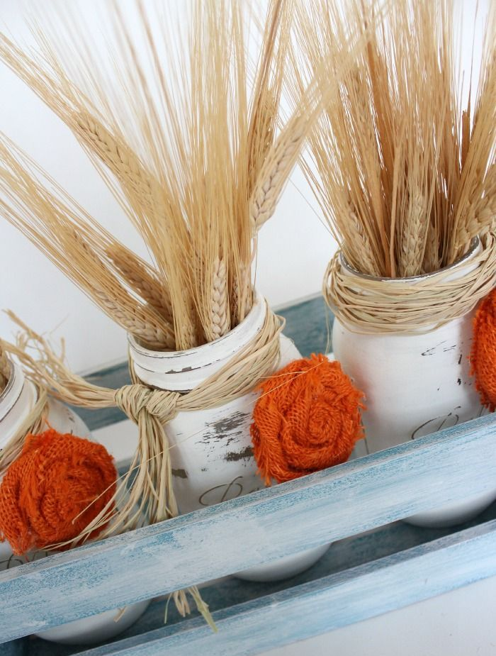 a chalked crate with white jars, orange fabric blooms and wheat is a chic and cozy centerpiece or decoration for a vintage farmhouse feel