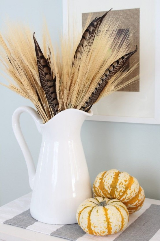 a white jug with wheat, feathers and mini pumpkins is a nice fall arrangement and centerpiece