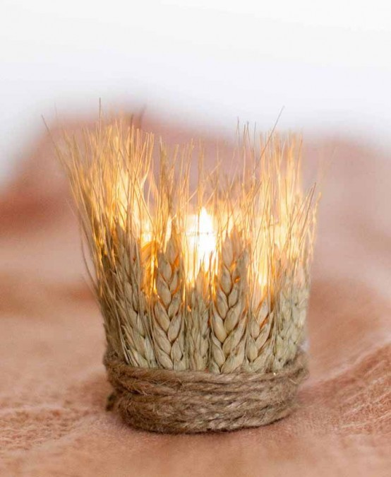 a glass candle holder covered with wheat and twine looks rustic and fall-like