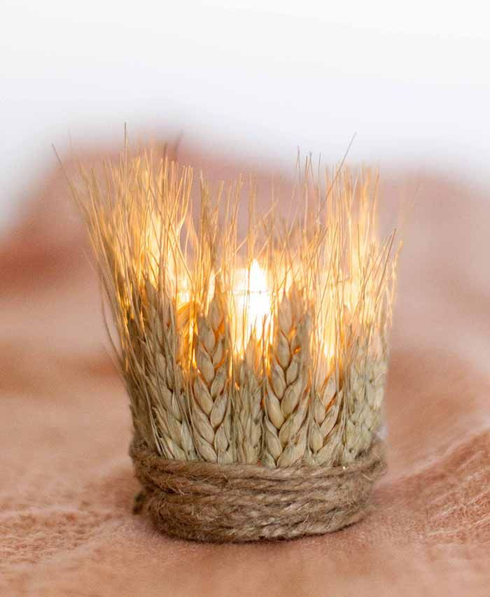 a glass candle holder covered with wheat and twine looks rustic and fall like