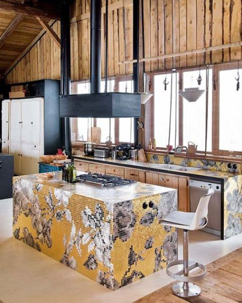a unique chalet kitchen clad with light-colored wood, dark metal appliances and colorful yellow and grey tiles forming mosaics on all the countertops