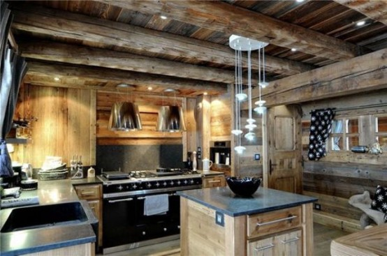 a light-colored chalet kitchen with wooden beams, stone countertops, built-in lights and pendant lamps