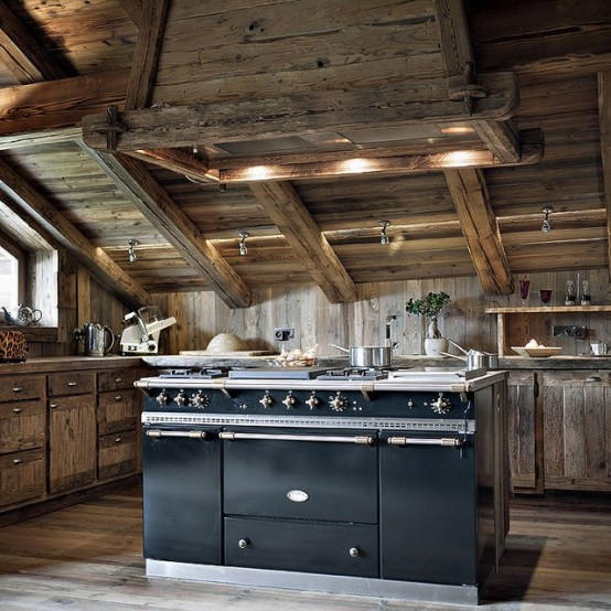 a rustic chalet kitchen all clad with reclaimed wood, with a large vintage kitchen island and built-in lights looks welcoming and cozy
