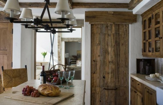 a reclaimed wood kitchen with a wooden table and stone countertops and a lamp hanging over the table