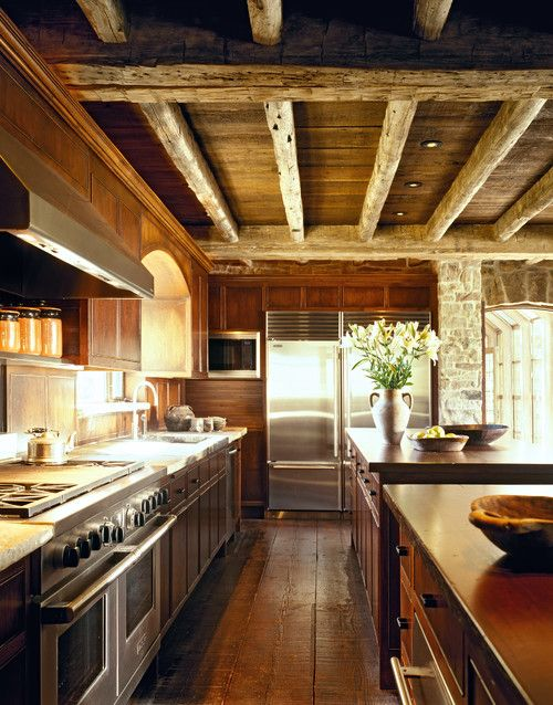 a cozy chalet kitchen all clad with wood, with wooden beams on the ceiling, with rustic and vintage furniture and built-in lights