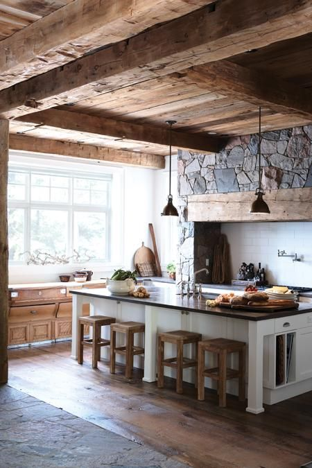 a cozy chalet kitchen with a wooden ceiling with beams and a stone statement wall for maximal coziness