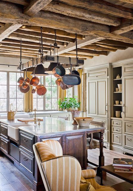 a neutral traditional kitchen with chalet touches - a wooden ceiling with beams, a dark stained kitchen island and pans hanging over the kitchen island