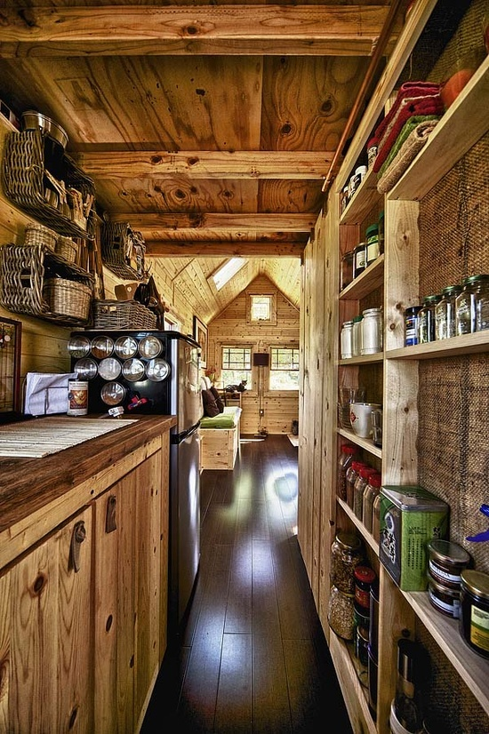 a small and narrow chalet kitchen with reclaimed wood, a burlap covered wall, wooden cabinets and a wooden ceiling with beams