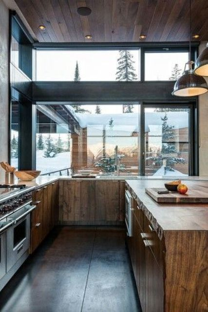 a contemporary chalet kitchen clad with reclaimed wood, with glazed walls, a wooden kitchen island and pendant lamps over it