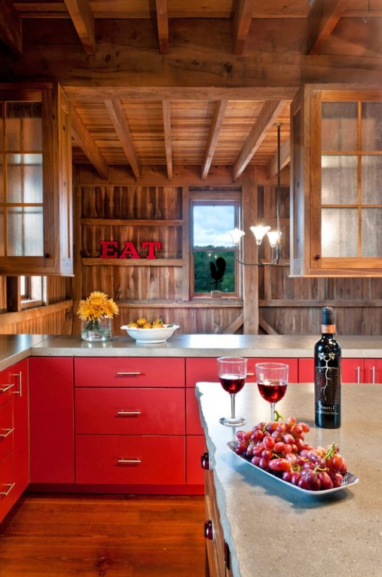 a creative and bright chalet kitchen clad with wood, with wooden beams, bright red cabinets and stone countertops looks bold and very cool