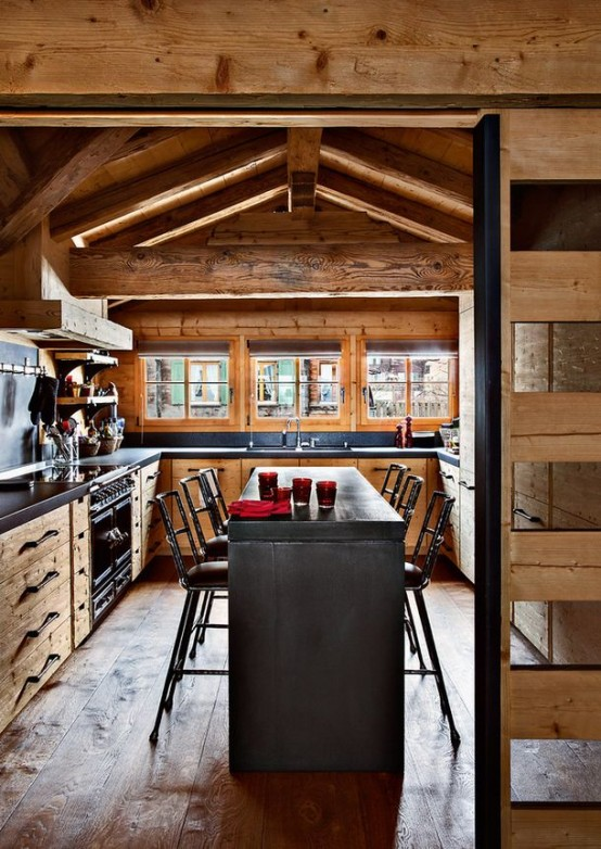 a cozy chalet kitchen decorated with reclaimed wood, with stone countertops, a stone kitchen island and a wooden screen or sliding door