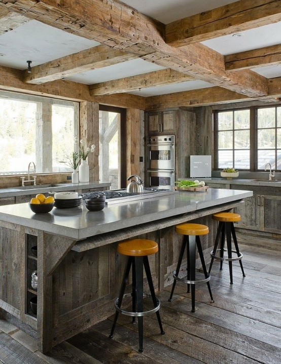 a traditional chalet kitchen clad with reclaimed wood, with wooden beams on the ceiling, with stone countertops and bright stools for a bold touch