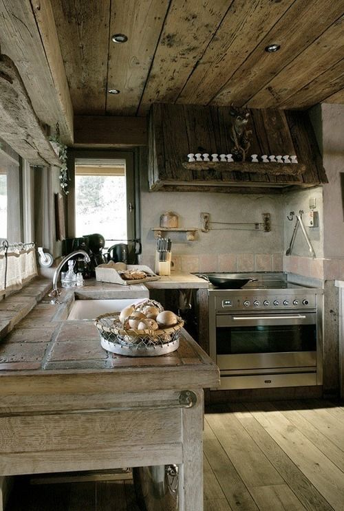 a rough chalet kitchen all clad with neutral reclaimed wood, with a rough wooden hood, with tiles on the countertops