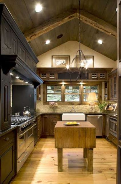 a cozy chalet kitchen with white stone walls, dark cabinets and a hood, a wooden kitchen island and built-in lights