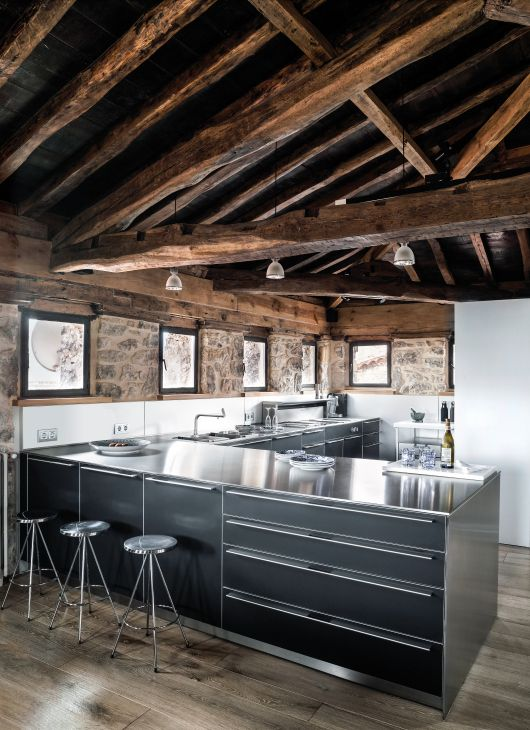a rough chalet kitchen with stone and wood walls, a wooden ceiling with beams, cabinets with metal countertops