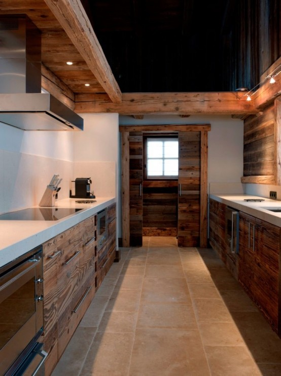 a reclaimed wood chalet kitchen with white stone countertops and built-in lights and metal handles looks unique