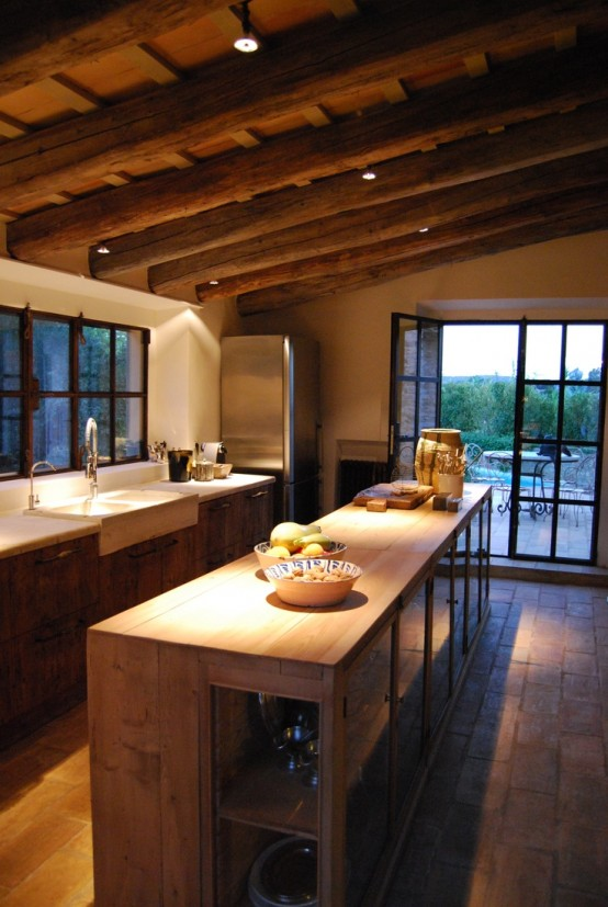 a chalet kitchen done with a wooden ceiling with beams, with matching furniture and whiet stone countertops