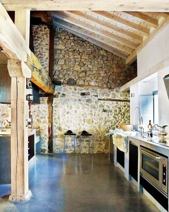 a chalet kitchen done with stone walls, with a wooden ceiling with beams and wooden beams right in the space is a cool idea for a chalet feel
