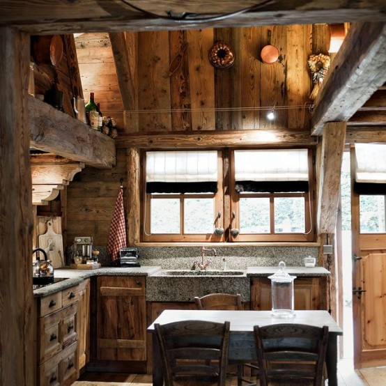 a cool chalet kitchen done with reclaimed wood, with wooden beams, stone countertops and some lights here and there