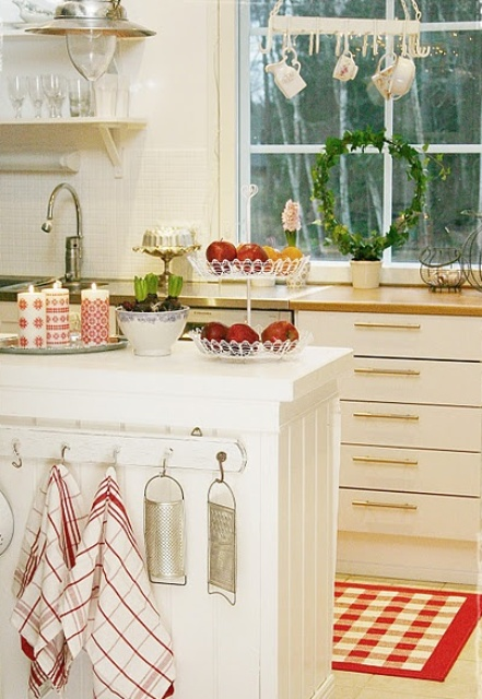 plaid red and white linens, red and white candles and an evergreen wreath add a holiday feel to the space