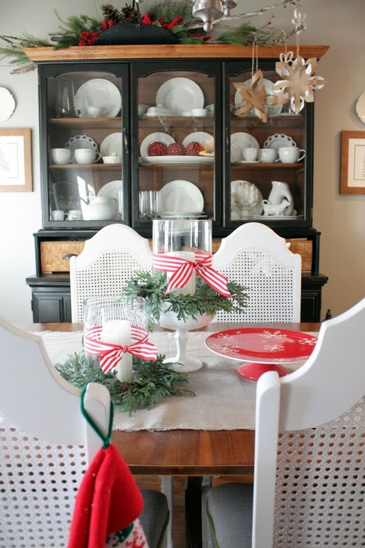 evergreens and red bows, a red stand, paper snowflakes and a Christmas arrangement with evergreens, berries and pinecones