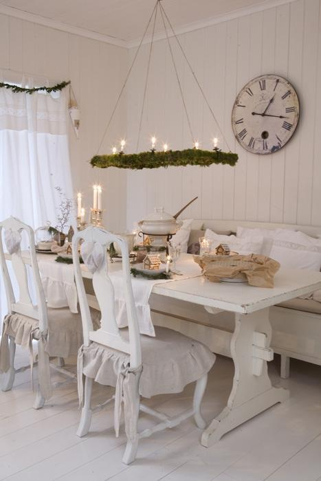 candles in candleholders, an evergreen hanging with lights and a gingerbread house for a Christmas feel in the kitchen