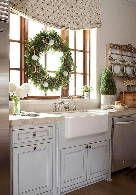 an evergreen Christmas tree and an evergreen wreath with white and silver ornaments for a Christmas feel in the space